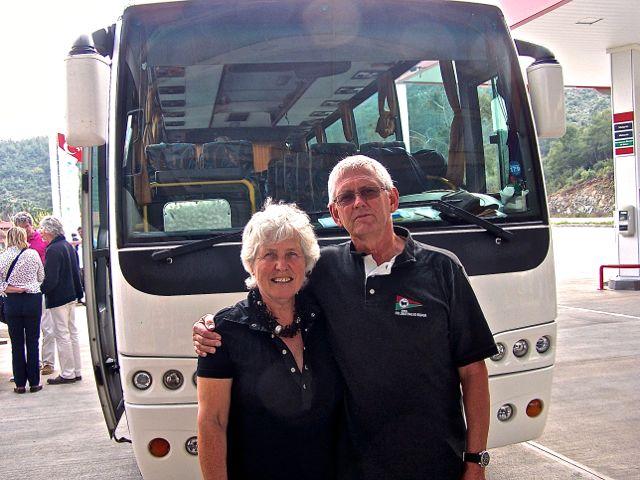Een typerende foto van een echtpaar op leeftijd dat een uitstapje maakt en even voor de bus poseert