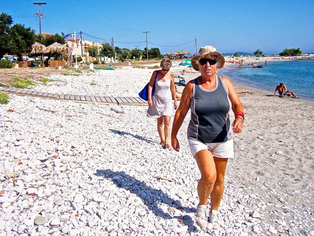 Ing stapt parmantig over het strand met d'r Afghanistan hoedje, Ann volgt
