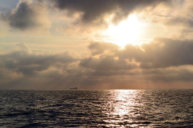 Je ziet de tanker nog in de verte onder de opkomende zon